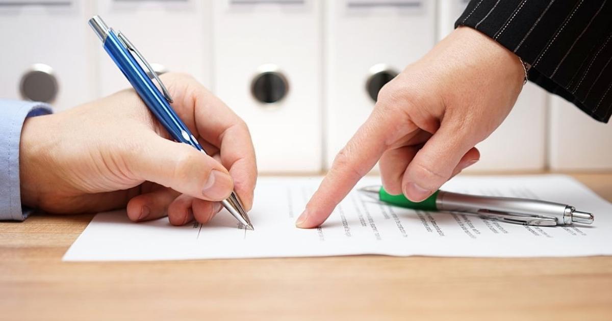 Duas pessoas em processo de assinatura para registro de imóveis
